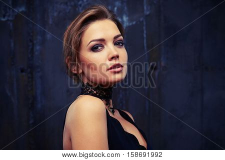 Close-up portrait of the irresistible deep regard of relaxed young good-looking female model who is posing at the camera