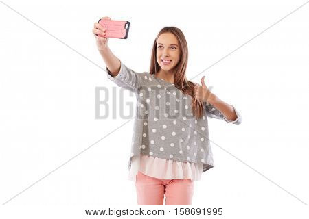 Mid shot of pretty Caucasian girl in cheerful mood is making selfie photo via smartphone isolated over white background