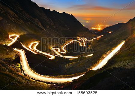Landscape from the rocky Fagaras mountains in Romania in the evening with Transalpina winding road in the distance
