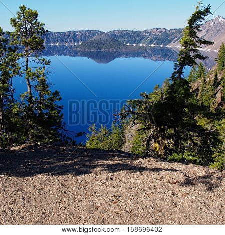 Wizard Island seen through the trees reflecting in Crater Lake on a sunny summer morning.