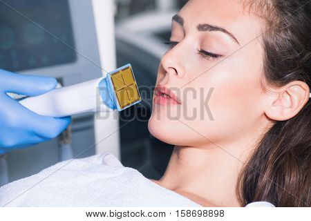 woman face fractional treatment at medical spa center