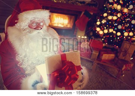 Santa Claus opening magic gift in home next Christmas tree