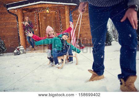 Happy children sledding at winter time-Family time