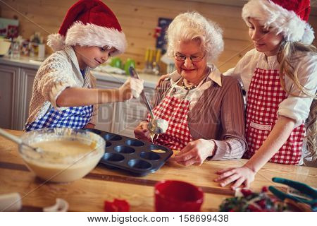 grandchildren enjoying with grandmother preparing Christmas cookies