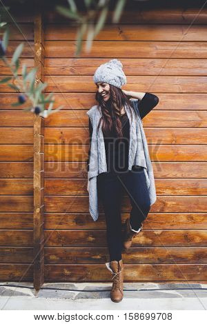 Young woman in a cabin with a warm fashion outfit.