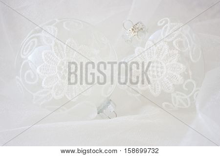 horizontal image of two clear glass Christmas ornaments decorated with white lace on a white sheer nylon background.