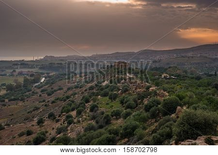 Sunset in Valley of temples in Agrigento in Sicily with clouds and night illumination.
