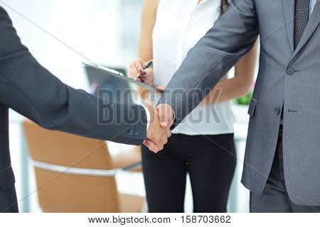 Successful handshake of business men in a working environment