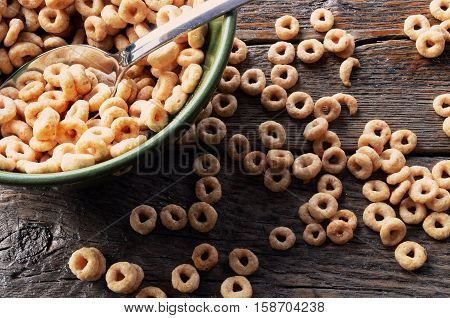 A close up image of a bowl of cereal with cereal spilled on the table surface.