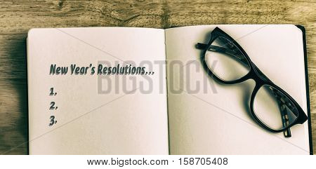 New years resolution list against overhead of reading glasses with notebook