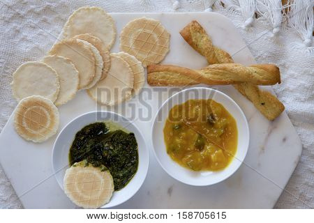 Pesto and pickles with savoury biscuits on a platter.