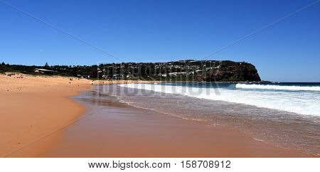 People relaxing on Copacabana Beach on a sunny day (Central Coast NSW Australia)