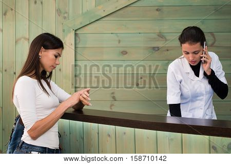 Portrait of female receptionist explaining form to patient in dentist clinic.