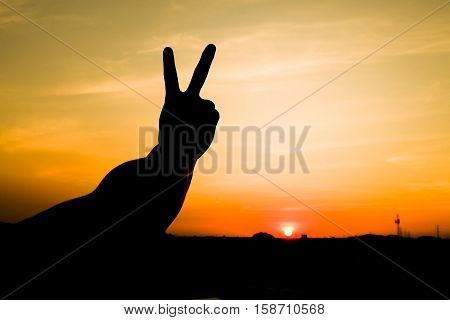 The silhouette of a man holding up two fingers to the sky at sunset. A symbol of peace and victory or fighting.