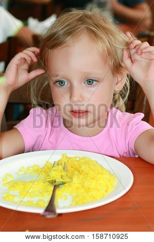 The girl ate the rice and no longer wants. The plate of rice on the table in front of the girl. Girl is looking detached gaze to the side. She doesn't want rice. Fed up. Full.