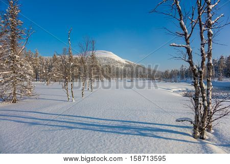 Sunny day Winter landscape with river and mountain - ski resort, Finland, Lapland