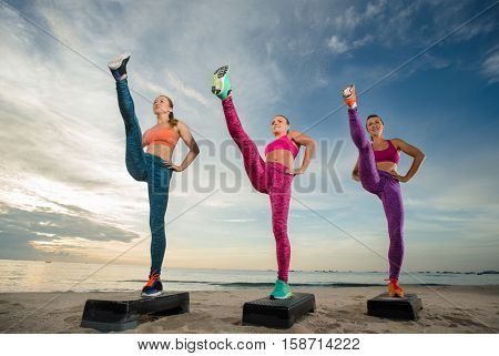 fitness, training, aerobics and people concept - group of girls working out with steppers on the beach