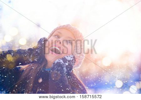 Winter girl portrait. Beauty Joyful Teenage Model Girl touching her face skin and laughing, having fun in winter park. Beautiful young woman laughing outdoors. Enjoying nature, wintertime