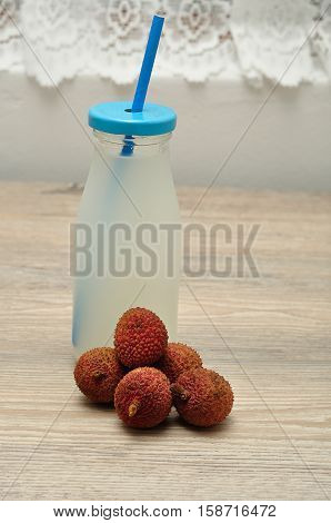 Litchi juice in a glass bottle with a blue straw and lid and fresh litchis
