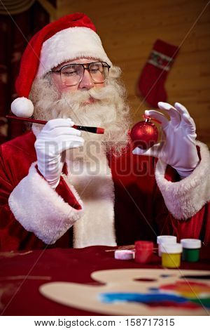 Santa Claus sitting at the table and decorating Christmas bauble