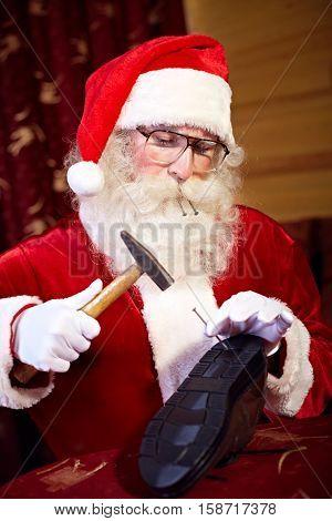 Santa Claus repairing shoe in his workshop