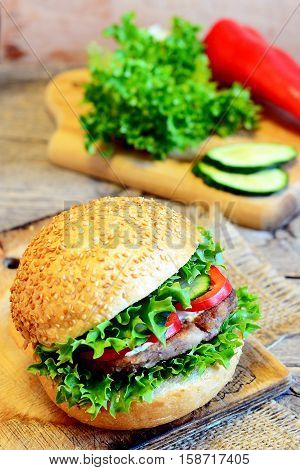 Sandwich with fried bean cutlet, green lettuce, red pepper and cucumber. Delicious sandwich and ingredients on a wooden board. Simple vegetarian breakfast sandwich recipe. Rustic style. Closeup