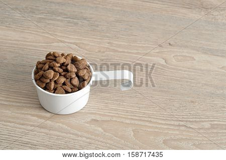 Dry dog food in a white mug isolated on a wooden background