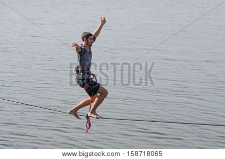DNEPR UKRAINE - OCTOBER 01 2016:Young rope-walker keeping balance on a rope under Dnepr river in center of the Dnepr city at October 01, 2016