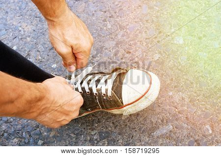 Runner tying shoelaces on sneakers, solar flare