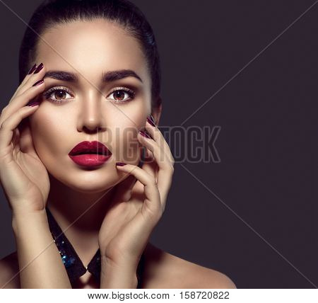 Beauty Brunette Woman with Perfect Makeup. Beautiful Professional Holiday Make-up. Red Lips and Nails, perfect eyebrows. Beauty Girl's Face isolated on dark background