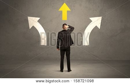 A confused businessman facing a grey urban wall with a yellow arrow pointing in the right direction concept