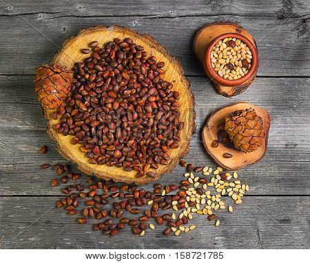 Pine nuts (cedar nuts) uncleaned on wooden frame. Peeled pine kernels on gray background rustic wooden table. Pine cones (cedar nuts) with nuts. Top view. Flat lay