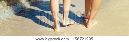 Legs of women walking on the sand of the beach