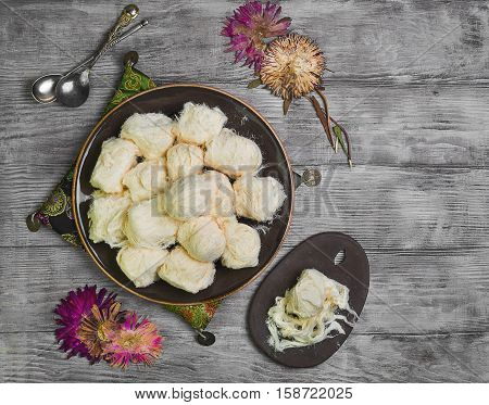 Turkish sweetness of sugar halvah pishmanie. Cloth for Turkish sweets decorative dried flowers. Portion Turkish sweets halva pishmanie on the board. Light white wooden background. Top view. Flat lay
