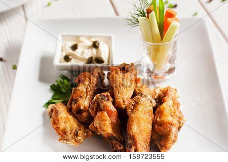 Grilled chicken wings with creamy sauce close-up. Tasty fried snack with fresh vegetables on white plate. Restaurant serving, junk food concept