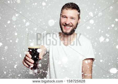 winter christmas people drink concept- Drunk tattooed bearded man in a white T-shirt isolated on a grey background. A guy with a glass. smiling man happy. over snow background