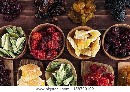 Assortment of dried fruits in spoons bowls on brown wooden background. Decorative border of dry exotic fruit. Top view.