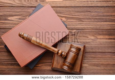Gavel with sound block and books on wooden background, top view