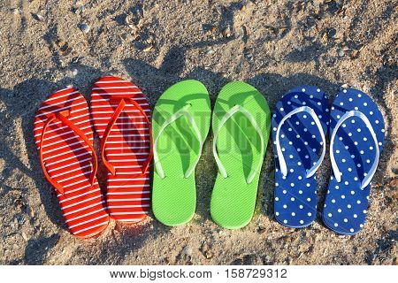 Colorful sandals on sea beach, close up view
