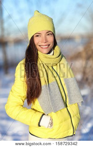 Happy cute Asian winter woman in snow wearing yellow fashion outerwear outfit with knit wool accessories hat, scarf, and down jacket. Chinese girl smiling outdoors. Healthy skin.