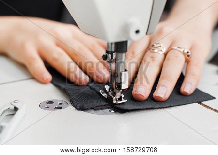 Woman hands with fabric at sewing machine. Seamstress working behind her equipment. Tailoring process, designer workshop, garment industry concept