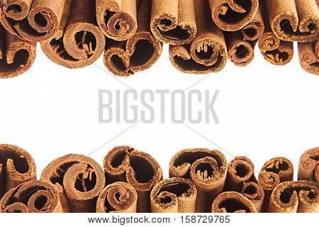 Cinnamon sticks closeup on white background. Isolated. Decorative border of cinnamon sticks spice.