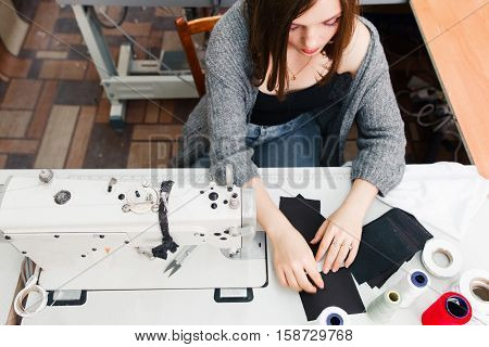 Seamstress working at sewing machine top view. Young female tailor working at her workplace. Tailoring process, designer workshop, garment industry concept