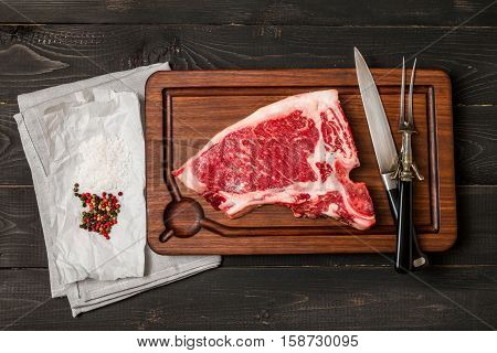 Raw fresh meat Club Steak, seasoning and meat fork and knife on dark wooden background, top view