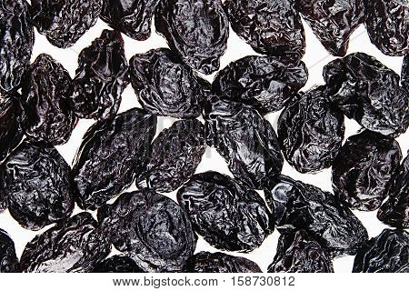 Prune closeup on white background. Heap of glossy black prunes. Top view.
