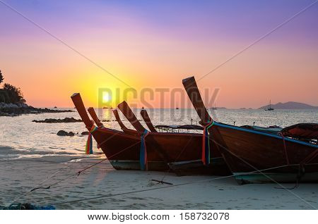 Colorful sunset with Thai traditional longtail boat on the beach and yacht and other boats in the sea in the evening at a high season of Lipe island Thailand with color filtered