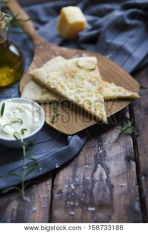 Focaccia with olive oil parmesan cheese white sause and rosemary. Homemade traditional Italian bread focaccia on the linen napkin.