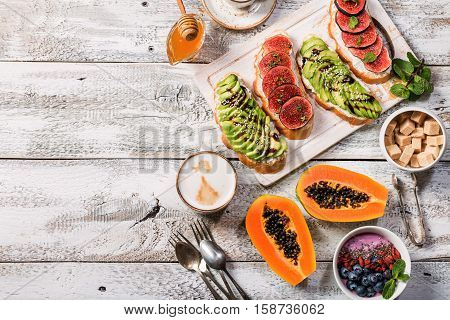 Healthy breakfast ingredients. Bowl of smoothie, fresh papaya, avocado and figs sandwiches , coffee and honey. Top view, copy space