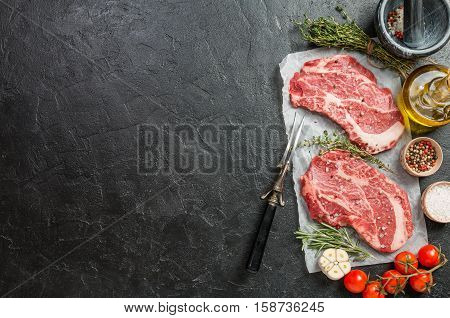 Two raw fresh marbled meat black angus steak ribeye and seasonings on black stone background. Top view