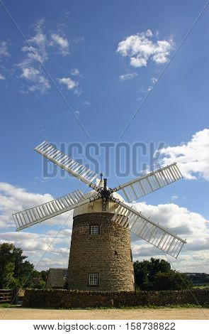 Heage windmill in Derbyshire from the front showing the cap and four out of the six sails (two missing) with a background of blue and grey sky with white clouds.